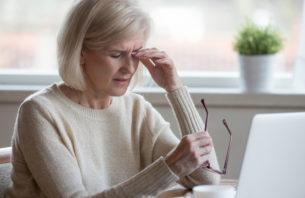 目元を抑えるパソコンに向かっている女性