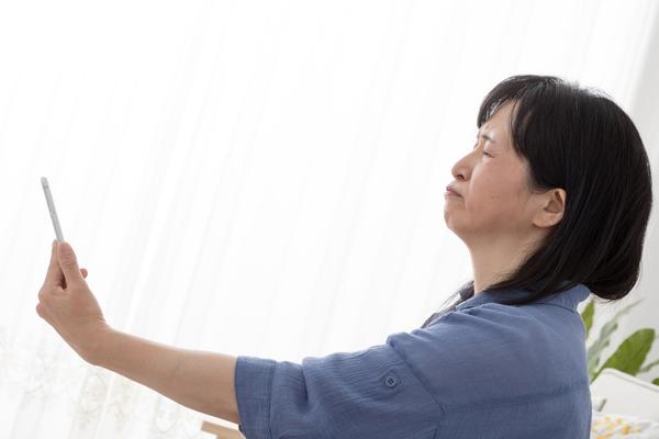 スマートフォンを自分から離して見る女性